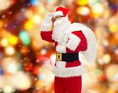 christmas, holidays and people concept - man in costume of santa claus with bag looking far away over red lights background