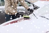 transportation, winter, people and vehicle concept - closeup of man cleaning snow from car with brush