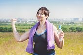 Fitness Plus Size Woman With Towel And Water Bottle