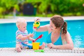 picture of shovel  - Happy family young active mother and adorable curly little baby having fun in a swimming pool playing with toy watering can and shovel enjoying summer vacation at a tropical resort - JPG