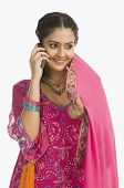 stock photo of salwar  - Woman wearing a salwar kameez and talking on a mobile phone - JPG