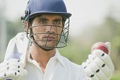 image of cricket  - Cricket batsman holding a cricket bat with a cricket ball - JPG