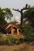 stock photo of mud-hut  - Mud huts with mausoleum in the background - JPG