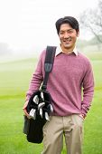picture of golf bag  - Golfer standing holding his golf bag smiling at camera at the golf course - JPG