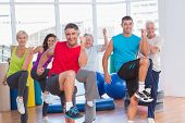 stock photo of senior class  - Portrait of fit people performing aerobics exercise in gym class - JPG