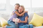 stock photo of daughter  - Portrait of happy mother with gift embracing daughter in house - JPG