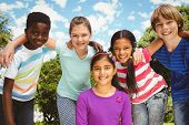 stock photo of huddle  - Portrait of happy children forming huddle at the park - JPG