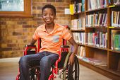 stock photo of wheelchair  - Portrait of little boy sitting in wheelchair at the library - JPG
