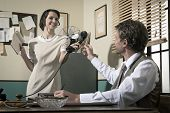 stock photo of 1950s style  - Smiling secretary passing phone receiver to her director 1950s vintage style office - JPG