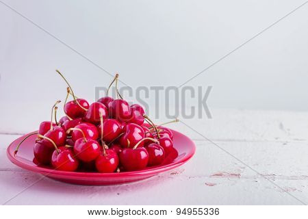 Ripe Cherries On A Red Plate. Selective Focus. poster
