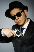 pic of top-gun  - Young man in classic striped costume holding gun isolated on gray - JPG