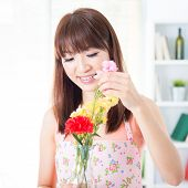 pic of apron  - Happy Asian housewife with apron arranging flowers to vase - JPG