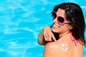 picture of sunbather  - Happy woman pointing sunscreen lotion funny smiley on her back and enjoying summer vacation at swimming pool - JPG