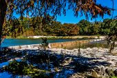 stock photo of crystal clear  - Bright Beautiful Fall Foliage On The Crystal Clear Frio River at Garner State Park Near the Low Water Dam - JPG