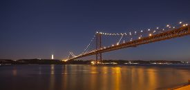 picture of bridge  - The 25th April bridge in Lisbon at night under a full moon - JPG