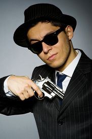 image of gangsta  - Young man in classic striped costume holding gun isolated on gray - JPG