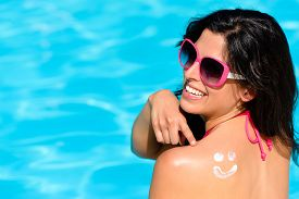 picture of sunbathers  - Happy woman pointing sunscreen lotion funny smiley on her back and enjoying summer vacation at swimming pool - JPG