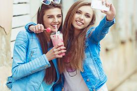 stock photo of  friends forever  - Hipster girlfriends taking a selfie in urban city context - JPG