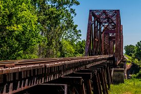image of trestle bridge  - An Interesting View of an Old Iconic Iron Truss Railroad Bridge Over the Brazos River - JPG