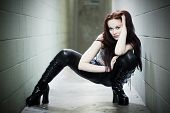 pic of gothic girl  - A leather clad model crouches in a run down hallway - JPG