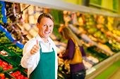 stock photo of grocery store  - Shop assistant in a supermarket at the vegetable shelf - JPG