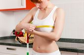 Thin woman measuring her chest with a tape measure, she seems to be unhappy