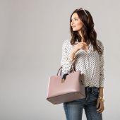 Young glamour woman wearing polka dot shirt and jeans posing with pink handbag. Beautiful stylish gi poster
