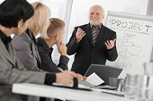 Senior businessman presenting on meeting to mid-adult coworkers, smiling, gesturing with both hands.?