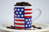 unground coffee beans in and around an American Flag cofee cup on white background