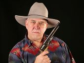 A cowboy poses for his portrait with his Colt Navy 44 caliber black powder revolver