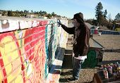 an unidentifiable person spray paints graffitti on