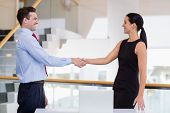 Business executives shaking hands with each other at conference centre poster
