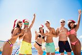 Cropped Shot Of Chilling, Dancing International Youth In Santa S Hats, Enjoying On Resort Beach Pool poster