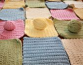 hand made crochet squares and yarn ready to be sewn into a baby blanket