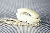 an old generic cream colored analog telephone sits on a black and white background waiting for someone to