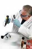 forensic analysis - a Forensics Examiner or Lab Technician checks a gun for evidence of a crime, loo