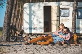 Hippie Young Couple Relaxing On Blanket Near Camper Van poster