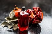 Close Up Of Essential Oil Of Pomegranate With Raw Ripe Pomegranate On Wooden Surface In Transparent poster