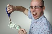 Man with scissors, cutting one dollar bill