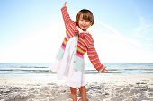 Small cute girl enjoying sunny day at the beach. Shoot against the sun.