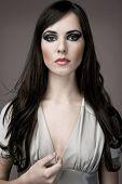 Young elegant brunette fashion model in designer dress.