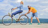 Learn Cycling With Support. Woman Rides Bicycle Sky Background. Man Helps Keep Balance And Ride Bike poster