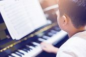 Blurry Picture Of Boy Play The Piano With Selective Focus poster