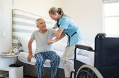 Smiling nurse assisting senior man to get up from bed. Caring nurse supporting patient while getting poster