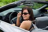 Beautiful Brunette Young Woman Driving A Sports Car