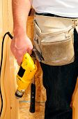 Contractor Wearing A Tool Belt And Holding A Power Drill