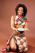 Bela jovem africana vestindo estilo tradicional Tribal roupa segurando uma tigela de arroz