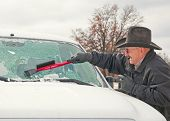 image of ice-scraper  - Man wearing a cowboy hat scraping ice off his vehicle windshield after an ice storm on a cold winter morning - JPG
