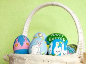 picture of duck egg blue  - Hand painted Easter eggs in basket against light green background - JPG