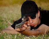 Young man aiming with a semiautomatic rifle, shallow depth of field on muzzle